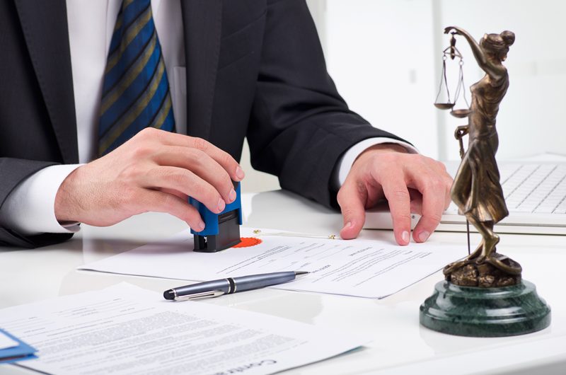 Nugen Law Lawyer stamping documents